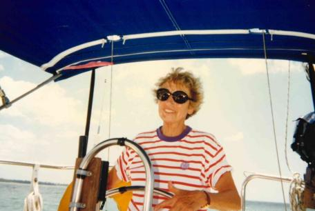 Marny smiling and happy at the helm of her and Bob's sail boat.